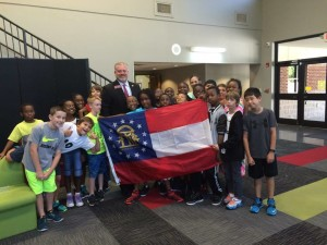 Rep. Gravley presenting the State Flag of Georgia to the Brighten Academy students.